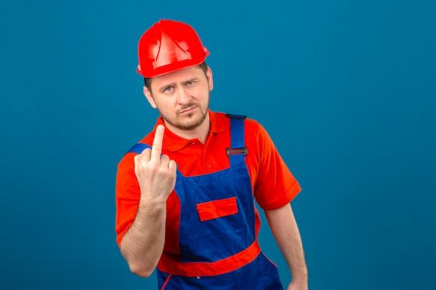 Uniforme d'uso della costruzione dell'uomo e casco di sicurezza dispiaciuti mostrando il dito medio alla macchina fotografica che controlla parete blu isolata