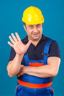 Uniforme da costruzione dell'uomo del costruttore e casco di sicurezza che mostrano e che indicano su con le dita numero cinque mentre sorridendo sicuro e felice sopra la parete blu isolata