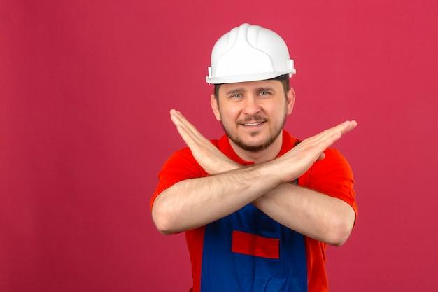 Uniforme da costruzione dell'uomo del costruttore e casco di sicurezza che stanno con le armi attraversate che fanno sorridere di gesto di arresto sicuro sopra la parete rosa isolata
