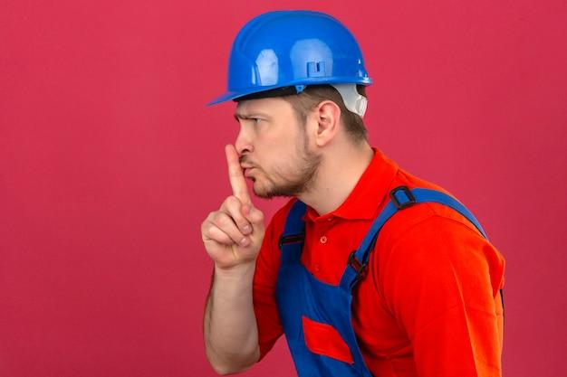 Uniforme da costruzione dell'uomo del costruttore e casco di sicurezza che stanno lateralmente chiedendo di essere calmo con il dito sul silenzio delle labbra e sul concetto segreto sopra la parete rosa isolata