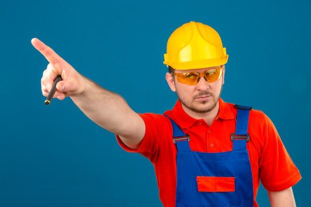Uniforme da costruzione e casco di sicurezza d'uso dell'uomo del costruttore che guardano da parte e che indicano con il dito qualcosa con l'espressione arrabbiata sul fronte che controlla parete blu isolata