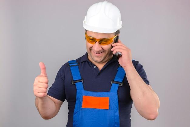 Uniforme da costruzione e casco di sicurezza d'uso dell'uomo del costruttore che parlano sul telefono cellulare felice e che sorride mostrando i pollici su sopra la parete bianca isolata