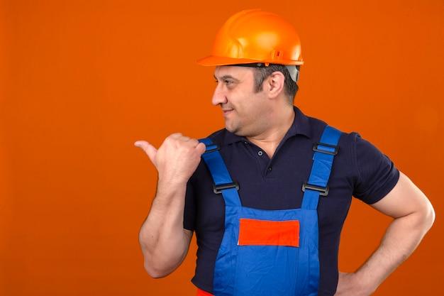 Uniforme da costruzione e casco di sicurezza d'uso dell'uomo del costruttore che sorridono con il fronte felice che guarda e che indica il lato con il pollice su sopra la parete arancio isolata