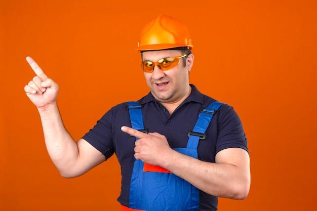Uniforme da costruzione e casco di sicurezza d'uso dell'uomo del costruttore che sorridono con il fronte felice e che indicano il lato con le dita sopra la parete arancio isolata