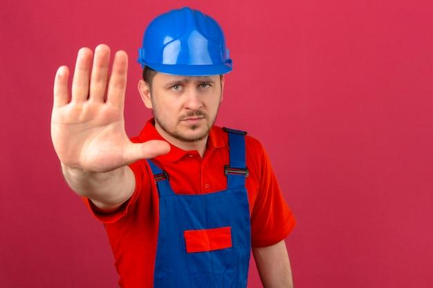 Uniforme da costruzione e casco di sicurezza d'uso dell'uomo del costruttore che stanno con la mano aperta che fa il fanale di arresto con il gesto serio e sicuro della difesa di espressione sopra la parete rosa isolata
