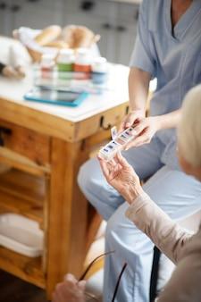 Uniforme da portare dell'infermiera che dà le pillole al paziente