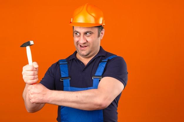 Uniforme di costruzione d'uso dell'uomo e casco di sicurezza del costruttore che stanno con il martello che sorride sopra la parete arancio isolata