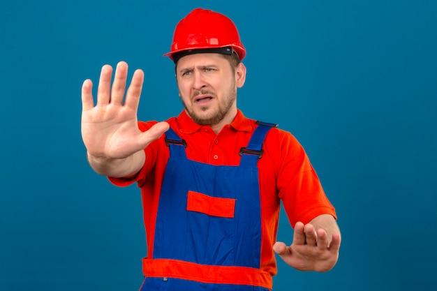 Uniforme edile d'uso del casco di sicurezza dell'uomo del costruttore dispiaciuto e spaventoso facendo il fanale di arresto con le mani che controllano parete blu isolata