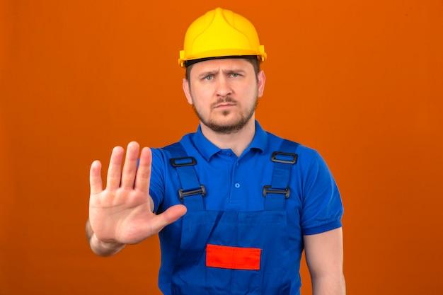 Uniforme edile d'uso del costruttore dell'uomo e casco di sicurezza che stanno con la mano aperta che fa il fanale di arresto con il gesto serio e sicuro della difesa di espressione sopra la parete arancio isolata