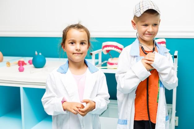 Uniforme medica della ragazza del ragazzino di smilg che gioca con lo stetoscopio