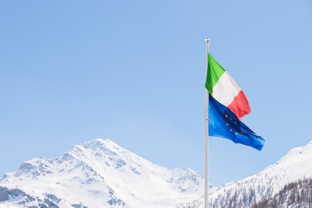 Unione europea e bandiera italiana che soffia nel vento sulle alpi