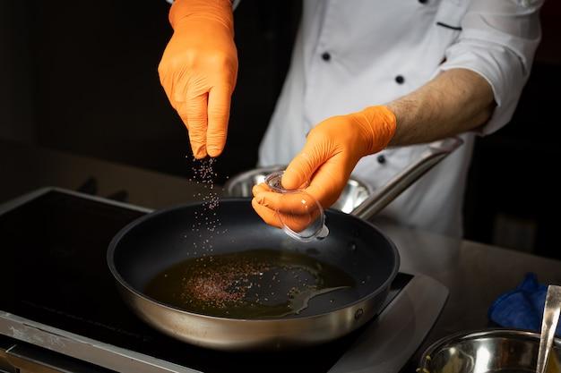 Uno chef con i guanti in mano aggiunge le spezie alla padella con il piatto di cottura