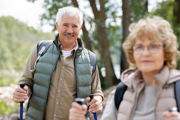 Uno degli escursionisti maturi che ti guarda mentre si gode un viaggio di fine settimana con sua moglie in un ambiente naturale