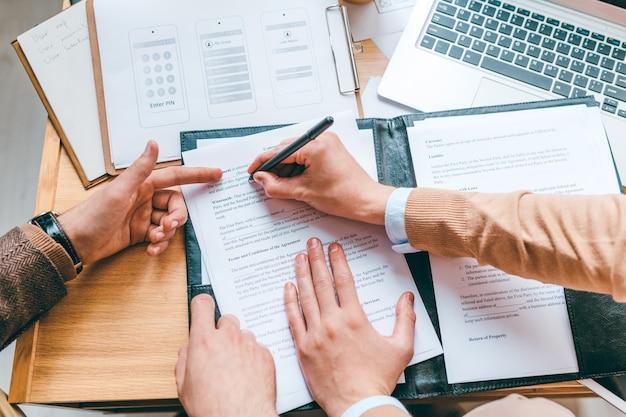 Uno dei partner commerciali che punta al contratto mentre il suo collega inserisce i dati personali prima di firmare il documento