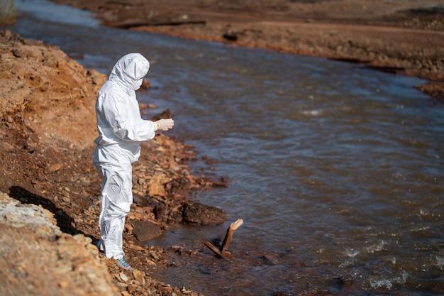 Uno scienziato in una tuta protettiva bianca preleva campioni d'acqua da un fiume inquinato.
