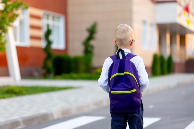 Uno scolaro biondo con uno zaino va a scuola. la vista dal retro