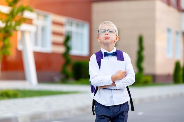 Uno scolaro con gli occhiali biondi con uno zaino e un libro bianco è in piedi a scuola