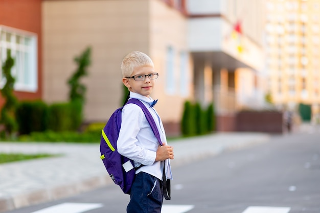 Uno scolaro con gli occhiali biondi e uno zaino è in piedi a scuola