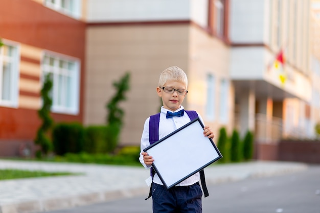 Uno scolaro felice con gli occhiali biondi e uno zaino si trova a scuola e tiene un cartello con un lenzuolo bianco.