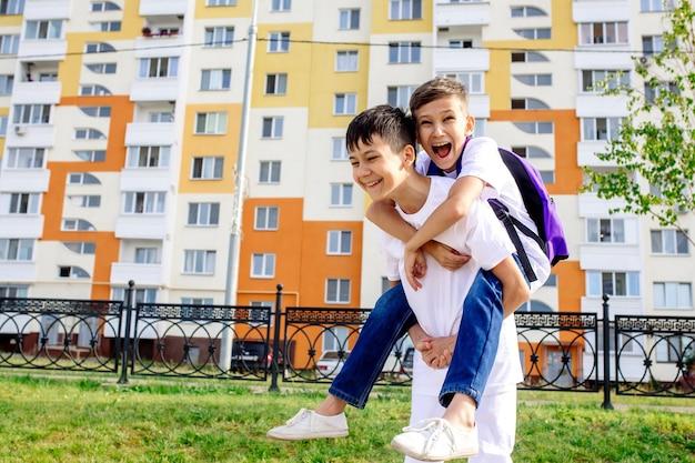 Uno scolaro porta il suo amico sulle spalle mentre va a scuola per strada in un nuovo quartiere
