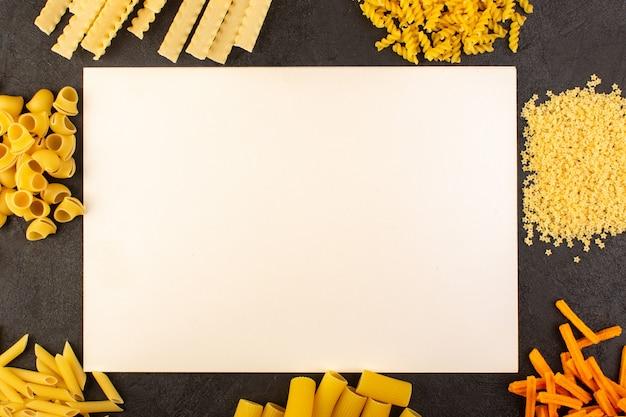 Uno scrittorio bianco di vista superiore di legno con la pasta cruda gialla formata differente isolata sulla pasta scura dell'italia dell'alimento del pasto del fondo