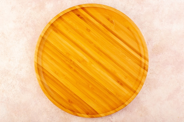 Uno scrittorio di legno vuoto di vista superiore marrone isolato sulla tabella di legno dell'albero del fondo rosa
