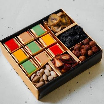 Uno scrittorio formato quadrato di vista superiore con noci e frutta secca sull'uva passa della frutta del dado dello scrittorio bianco