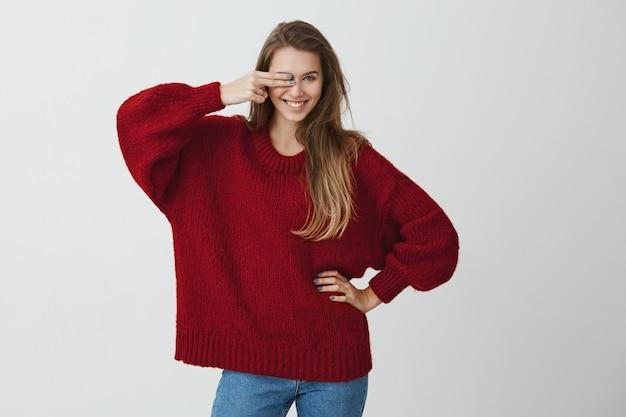 Uno sguardo e non hai possibilità. ragazza emotiva di bell'aspetto in maglione sciolto rosso che copre l'occhio con il gesto della pistola, sorridendo ampiamente e flirtando, guardando sensualmente.