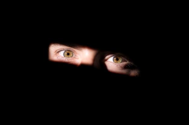 Uno sguardo fuori dal buio, gli occhi su uno sfondo nero