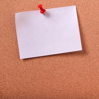 Uno spazio appiccicoso bianco della bacheca del sughero appuntato nota appiccicosa bianca della posta