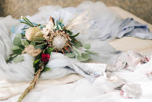 Uno splendido abito da sposa delicato con perline e pizzo si trova accanto a un bouquet di proteus.