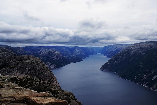 Uno splendido scenario delle famose scogliere preikestolen vicino a un lago sotto un cielo nuvoloso a stavanger, norvegia