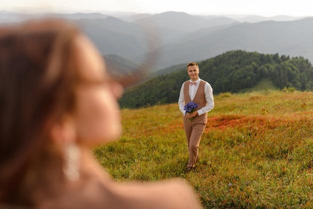 Uno sposo con un mazzo di fiori selvatici guarda la sua sposa. fotografia di matrimonio in montagna.