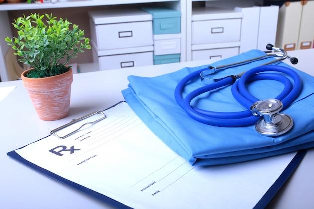 Uno stetoscopio medico e una prescrizione rx giacciono su un'uniforme medica