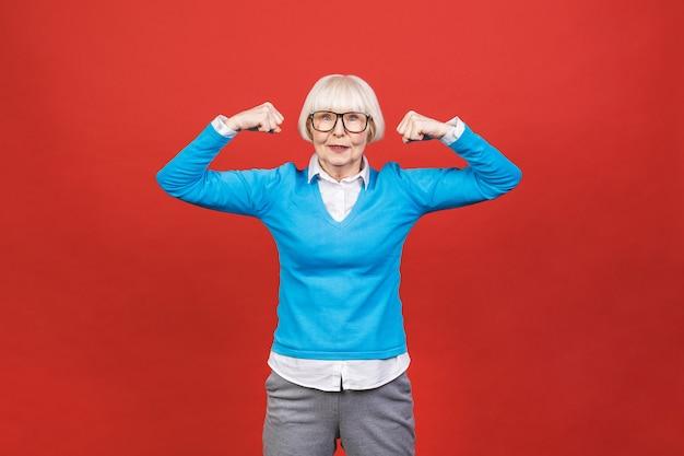 Uno stile di vita sano. donna invecchiata senior anziana felice che mostra al suo muscolo armi forti.