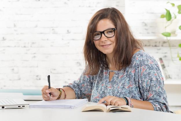 Uno studente con gli occhiali che lavora nel suo ufficio