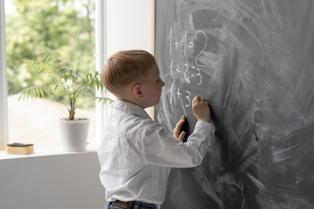 Uno studente moderno in classe scrive esempi di matematica sulla lavagna.