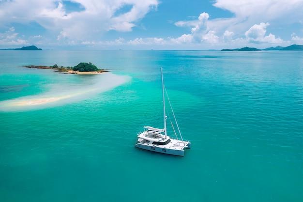 Uno yacht a vela solitario alla deriva nell'oceano azzurro caldo, in direzione di una misteriosa isola verde nel mezzo dell'oceano. in viaggio. vacanze di lusso. paesi caldi. paradiso. turismo.