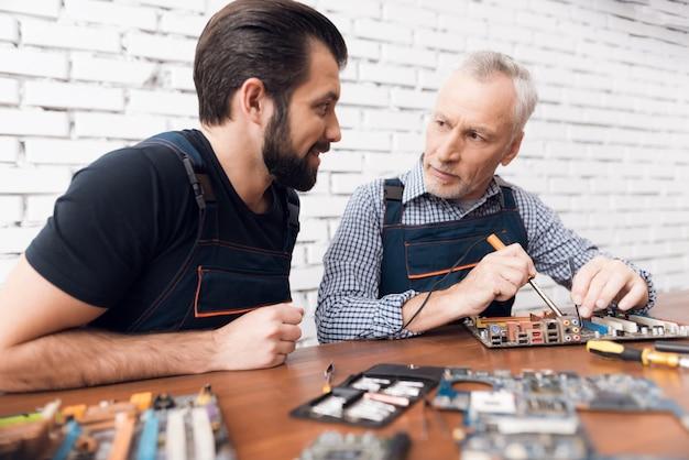 Uomini adulti e giovani riparano insieme le parti dal computer.
