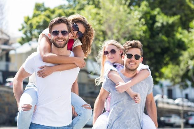 Uomini alla moda che fanno le spalle alle loro amiche per strada