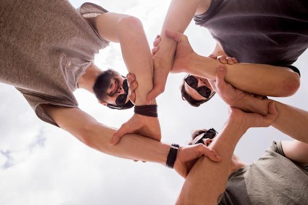 Uomini allegri che uniscono le mani insieme