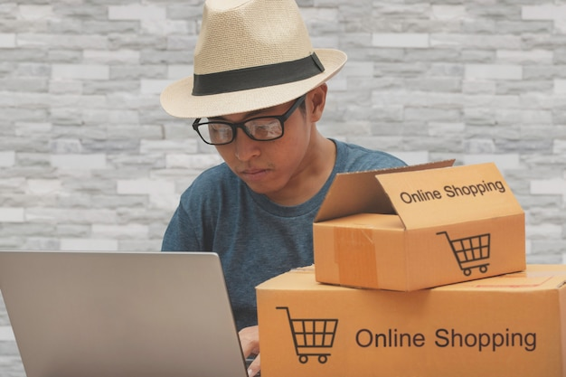 Uomini asiatici che controllano gli ordini di acquisto online dell'acquisto dai clienti.