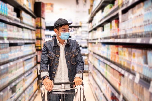 Uomini asiatici comprano e acquistano cibo per accumularsi durante l'epidemia di covid