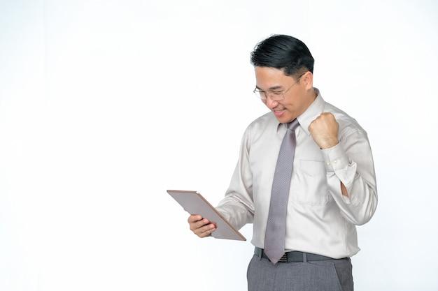 Uomini asiatici di mezza età felici che per mezzo delle compresse su un bianco