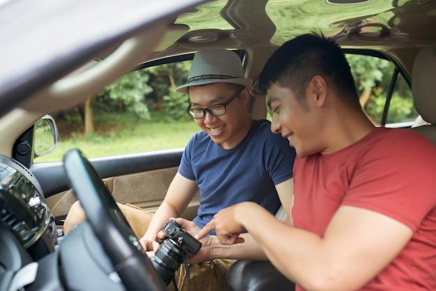Uomini asiatici felici che si siedono in automobile e che esaminano insieme macchina fotografica