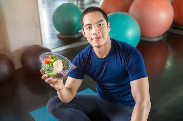 Uomini asiatici hansome con una ciotola di insalata di verdure in palestra.