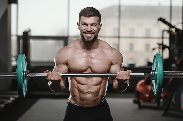 Uomini atletici brutali del culturista che pompano i muscoli con le teste di legno