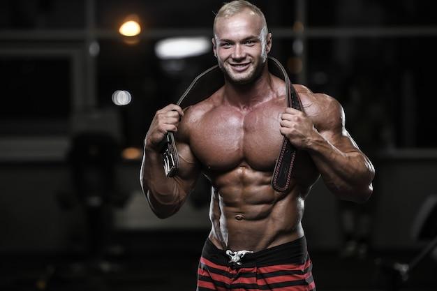 Uomini atletici del forte culturista bello che pompano i muscoli con le teste di legno