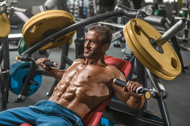 Uomini atletici di forte bodybuilder invecchiato brutale che pompano i muscoli con le teste di legno