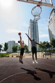 Uomini attivi che giocano a pallacanestro a colpo lungo